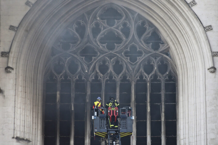 Fire fighters brigade work to extinguish the blaze at the Gothic St. Peter and St. Paul Cathedral, in Nantes, western France, Saturday, July 18, 2020. The fire broke, shattering stained glass windows and sending black smoke spewing from between its two towers of the 15th century, which also suffered a serious fire in 1972. The fire is bringing back memories of the devastating blaze in Notre Dame Cathedral in Paris last year that destroyed its roof and collapsed its spire and threatened to topple the medieval monument. (AP Photo/Romain Boulanger)