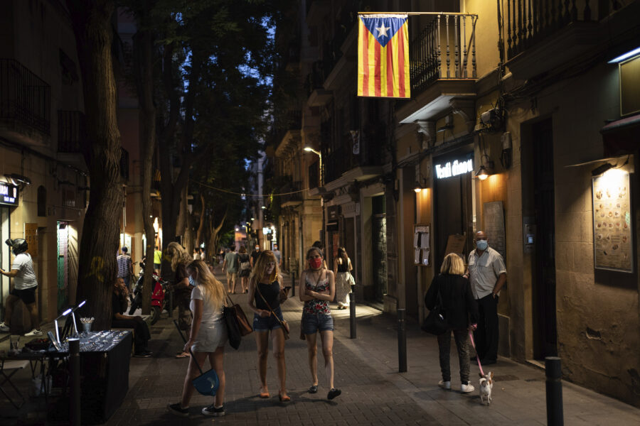People walk at night in Gracia neighborhood in Barcelona, Spain, Friday, July 24, 2020. Health authorities in the northeastern region of Catalonia have ordered nightclubs to be fully closed and bars and restaurant in Barcelona to shut down by midnight in an effort to stem the spread of the new coronavirus. (AP Photo/Felipe Dana)