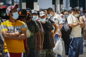 Pedestrians wearing protective masks wait in line for food donations during the COVID-19 pandemic, Tuesday, June 23, 2020, in the Corona neighborhood of the Queens borough of New York. (AP Photo/John Minchillo)