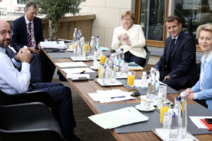 European Council President Charles Michel, left, poses for photographers with German Chancellor Angela Merkel, third right, French President Emmanuel Macron, second right and European Commission President Ursula von der Leyen, right, prior to a meeting on the sidelines of an EU summit at the European Council building in Brussels, Sunday, July 19, 2020. Leaders from 27 European Union nations meet face-to-face for a third day of an EU summit to assess an overall budget and recovery package spread over seven years estimated at some 1.75 trillion to 1.85 trillion euros. (AP Photo/Francois Walschaerts, Pool Photo via AP)