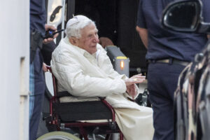 """Emeritus Pope Benedict XVI is pushed in to a bus in a wheelchair, in Regensburg, Germany, Thursday, June 18, 2020.  The Vatican says Emeritus Pope Benedict is in Germany to be with his brother, who is in poor health. Benedict on Thursday arrived in Regensburg, Germany, where his brother, the Rev. Georg Ratzinger, lives, and where """"he will spend the necessary time,"""" the Vatican said in a statement. (Daniel Karmann/dpa via AP)"""