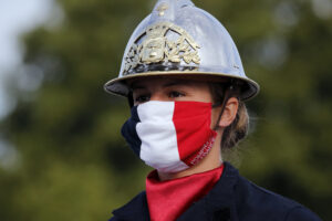A firefighter wears a face mask with the colors of the French flag, prior to the Bastille Day parade Tuesday, July 14, 2020 on the Champs Elysees avenue in Paris. France are honoring nurses, ambulance drivers, supermarket cashiers and others on its biggest national holiday Tuesday. Bastille Day's usual grandiose military parade in Paris is being redesigned this year to celebrate heroes of the coronavirus pandemic. (AP Photo/Christophe Ena, Pool)