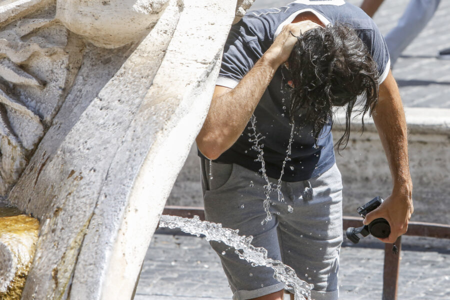 A man refreshes at the Barcaccia fountain, built between 1627 and 1629 by Pietro Bernini, possibly with the help of his son Gian Lorenzo, in downtown Rome, Friday, July 31, 2020. The first heat wave of the summer will last at least until Saturday, bringing temperatures over 34 Celsius (104 Fahrenheit). (AP Photo/Riccardo De Luca)