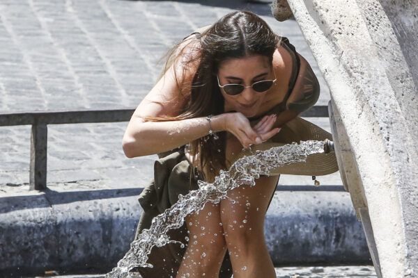 A woman drinks at the Barcaccia fountain, built between 1627 and 1629 by Pietro Bernini, possibly with the help of his son Gian Lorenzo, in downtown Rome, Friday, July 31, 2020. The first heat wave of the summer will last at least until Saturday, bringing temperatures over 34 Celsius (104 Fahrenheit). (AP Photo/Riccardo De Luca)