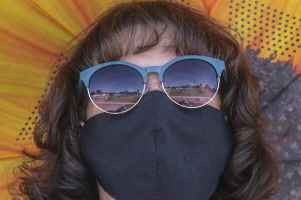 A woman wears a mask as she watches a AA American Legion game at Melaleuca Field in Idaho Falls, Idaho on Friday, July 31, 2020. (John Roark/The Idaho Post-Register via AP)
