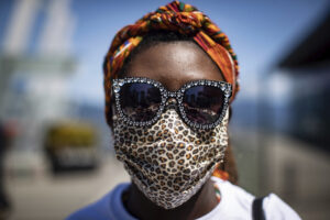 Maayaa Quist-Adade wears a face covering and sunglasses decorated with hearts during the coronavirus pandemic as she attends an Emancipation Day March, in Vancouver, on Saturday, Aug. 1, 2020. Emancipation Day marks the abolition of slavery in parts of the British Empire. The Slavery Abolition Act went into effect on August 1, 1834, after receiving Royal Assent nearly a year earlier. (Darryl Dyck/The Canadian Press via AP)