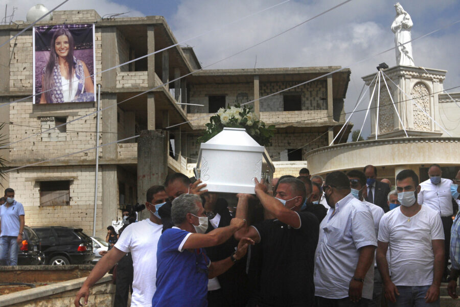 """Relatives of Nicole al-Helou, who was killed by the explosion Tuesday that hit the seaport of Beirut, carry her coffin during her funeral, in Sarba village, southern Lebanon, Thursday, Aug. 6, 2020. French President Emmanuel Macron said an independent, transparent investigation into the massive explosion in Beirut is """"owed to the victims and their families"""" by Lebanese authorities. During Macron's visit to the city on Thursday, angry crowds approached him and the Beirut governor as they walked through a blast-torn street. (AP Photo/Mohammed Zaatari)"""