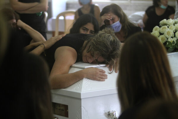 "The mother of Nicole al-Helou, who was killed by the explosion Tuesday that hit the seaport of Beirut, mourns on her daughter's coffin during her funeral, in Sarba village, southern Lebanon, Thursday, Aug. 6, 2020. French President Emmanuel Macron said an independent, transparent investigation into the massive explosion in Beirut is ""owed to the victims and their families"" by Lebanese authorities. During Macron's visit to the city on Thursday, angry crowds approached him and the Beirut governor as they walked through a blast-torn street. (AP Photo/Mohammed Zaatari)"
