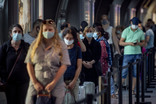 Passengers queue at a Corona test center at the airport in Frankfurt, Germany, Friday, Aug. 7, 2020. From Saturday on travelers coming back from one of the high-risk-countries have to do a Covid-19 test. (AP Photo/Michael Probst)