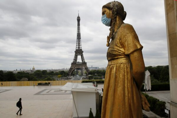 FILE- In this file photo dated Monday, May 4, 2020, a statue wears a mask along Trocadero square close to the Eiffel Tower in Paris. Britain will require all people arriving from France to isolate for 14 days – an announcement that throws the plans of tens of thousands of holiday makers into chaos. The government said late Thursday Aug. 13, 2020 that France is being removed from the list of nations exempted from quarantine requirements because of a rising number of coronavirus infections, which have surged by 66% in the past week.(AP Photo/Christophe Ena, File)