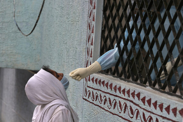 A woman gets her nasal swab sample taken for COVID-19 test at a government health center in Hyderabad, India, Sunday, Aug. 16, 2020. India is the third hardest-hit country by the pandemic in the world after the United States and Brazil. (AP Photo/Mahesh Kumar A.)