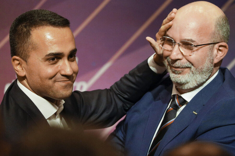 Italy's Foreign Minister and 5-Star Movement leader Luigi Di Maio, left, embraces his successor Vito Crimi at a meeting in Rome, Wednesday, Jan. 22, 2020, where Di Maio stepped down as party leader following a string of parliamentary defections, falling poll numbers and questions about the movement's future. Luigi Di Maio said he had finished his work, that an era had ended, and that he would trust his successor to lead the party going forward. (AP Photo/Andrew Medichini)