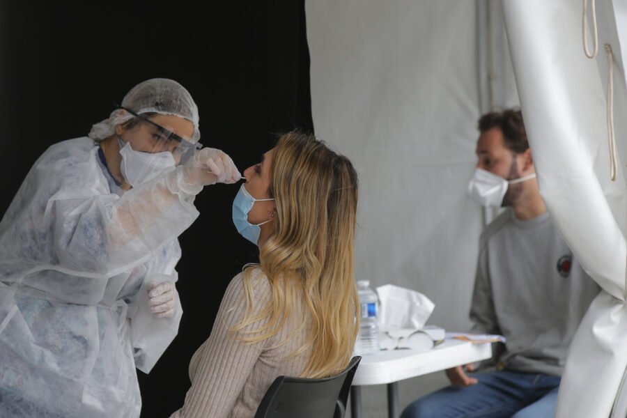 A medical technician administer a nasal swab to a woman at a mobile testing site outside the city hall in Paris, Monday, Aug. 31, 2020. With virus cases rising, France is struggling to administer enough tests to keep up with demands. (AP Photo/Michel Euler)