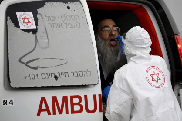 An Israeli medical worker wearing protective gear takes a swab from an ultra-Orthodox Jewish man for a coronavirus test, as part of the government's measures to stop the spread of the virus, in the Orthodox city of Bnei Brak, a suburb of Tel Aviv, Israel, Tuesday, March 31, 2020. The new coronavirus causes mild or moderate symptoms for most people, but for some, especially older adults and people with existing health problems, it can cause more severe illness or death. (AP Photo/Ariel Schalit)