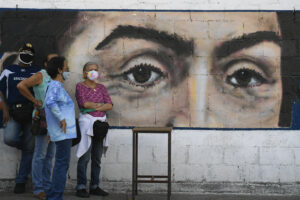 People wearing masks to curb the spread of COVID-19 wait to vote in front of a mural of the eyes of Venezuelan independence hero Simon Bolivar during a voting rehearsal at a public school in the Catia neighborhood of Caracas, Venezuela, Sunday, Oct. 25, 2020. Venezuela's electoral authority is testing the voting process in preparation for the Dec. 6 parliamentary elections. (AP Photo/Matias Delacroix)