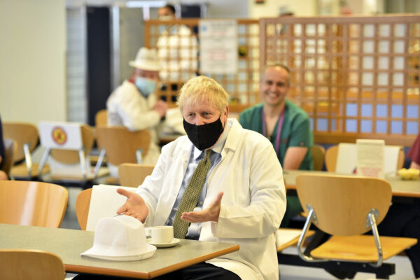 Britain's Prime Minister Boris Johnson speaks to members of staff in the canteen during a visit to Royal Berkshire Hospital, Reading, England, Monday Oct. 26, 2020, to mark the publication of a new review into hospital food. (Jeremy Selwyn/Pool via AP)