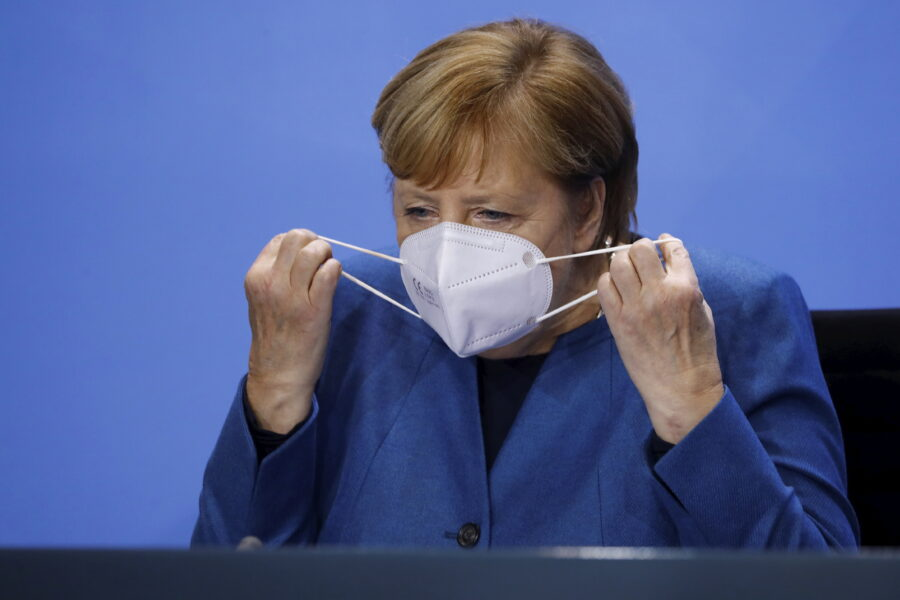 German Chancellor Angela Merkel (CDU) takes off her mask after a press conference at the Chancellery in Berlin, Wednesday, Oct. 28, 2020. Merkel is pressing for a partial lockdown as the number of newly recorded infections in the country hit another record high Wednesday. (Fabrizio Bensch/pool photo via AP)