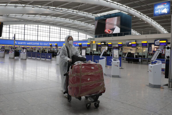 A traveller in protective clothing carries her luggage at Heathrow Airport in London, Wednesday, March 18, 2020. Britain's Foreign Secretary Dominic Raab has taken the decision to advise British nationals against non-essential travel globally for an initial period of 30 days, and of course subject to ongoing review. For most people, the new coronavirus causes only mild or moderate symptoms, such as fever and cough. For some, especially older adults and people with existing health problems, it can cause more severe illness, including pneumonia.(AP Photo/Frank Augstein)
