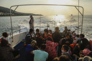 "Migrants sit on a Turkish coast guard vessel after they were pulled off life rafts, during a rescue operation in the Aegean Sea, between Turkey and Greece, Saturday, Sept. 12, 2020. Turkey is accusing Greece of large-scale pushbacks at sea — summary deportations without access to asylum procedures, in violation of international law. The Turkish coast guard says it rescued over 300 migrants ""pushed back by Greek elements to Turkish waters"" this month alone. Greece denies the allegations and accuses Ankara of weaponizing migrants. (AP Photo/Emrah Gurel)"