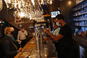 A bartender, wearing a face mask to fight against the spread of the coronavirus, serves a beer to a customer in a pub in Brussels, Wednesday, Oct. 7, 2020. Since bars in Brussels were forced to close as of Thursday for at least a month to deal with a massive surge in coronavirus cases while restaurants were allowed to remain open, the big question on the streets is: when is a bar a bar and when is a bar a restaurant. (AP Photo/Francisco Seco)