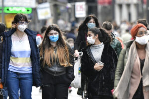 People walk with face masks to protect against coronavirus, in Cologne, Germany, Sunday, Oct. 11, 2020. Germany's 4th largest city reported exceeding the important warning level of 50 new infections per 100,000 inhabitants in seven days. More and more German cities become official high risk corona hotspots with travel restrictions within Germany. (AP Photo/Martin Meissner)