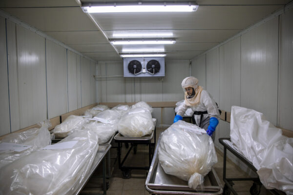 """A worker from """"Hevra Kadisha,"""" Israel's official Jewish burial society, prepares bodies before a funeral procession at a special morgue for COVID-19 victims, during a nationwide lockdown to curb the spread of the coronavirus, in the central Israeli city of Holon, near Tel Aviv, Monday, Oct. 12, 2020. (AP Photo/Oded Balilty)"""