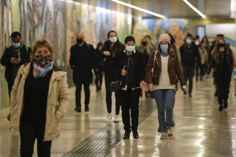 People wear masks to prevent the spread of COVID-19 as they walk in the underground of the Garibaldi railway station, in Milan, Italy, Tuesday, Oct. 13, 2020. Italian Premiere Giuseppe Conte ordered strict new anti-COVID measures early Tuesday, including limits on private gatherings and a ban on casual pickup sports. (AP Photo/Luca Bruno)