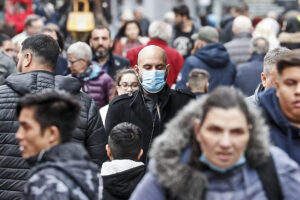 A man walks on a shopping street with a face mask due to the coronavirus pandemic in Gelsenkirchen, Germany, Wednesday, Oct. 14, 2020. The city exceeded the important warning level of 50 new infections per 100,000 inhabitants in seven days. More and more German cities become official high risk corona hotspots with travel restrictions within Germany. (AP Photo/Martin Meissner)