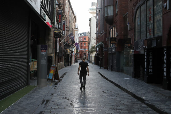 A lone man walks, past the famous Cavern club and other closed pubs and bars as new anti-coronavirus measures are set to come into force in Liverpool, England, Wednesday, Oct. 14, 2020. (AP Photo/Frank Augstein)
