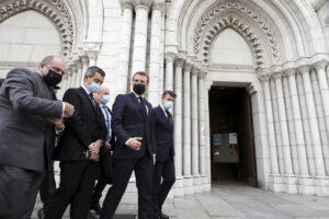 French President Emmanuel Macron, second right, Nice mayor Christian Estrosi, right, French Interior Minister Gerald Darmanin, second left, and Justice Minister Eric Dupond-Moretti arrive at Notre Dame church in Nice, southern France, Thursday, Oct. 29, 2020. An attacker armed with a knife killed at least three people at a church in the Mediterranean city of Nice, prompting the prime minister to announce that France was raising its security alert status to the highest level. It was the third attack in two months in France amid a growing furor in the Muslim world over caricatures of the Prophet Muhammad that were re-published by the satirical newspaper Charlie Hebdo. (Eric Gaillard/Pool via AP)
