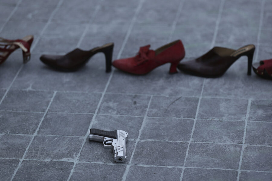 """A toy gun is placed near a line of red shoes representing murdered women, as part of a performance during the national women's strike """"A Day Without Women"""" in Mexico City, Monday, March 9, 2020. Thousands of women across Mexico went on strike after an unprecedented number of girls and women hit the streets to protest rampant gender violence on International Women's Day. (AP Photo/Fernando Llano)"""