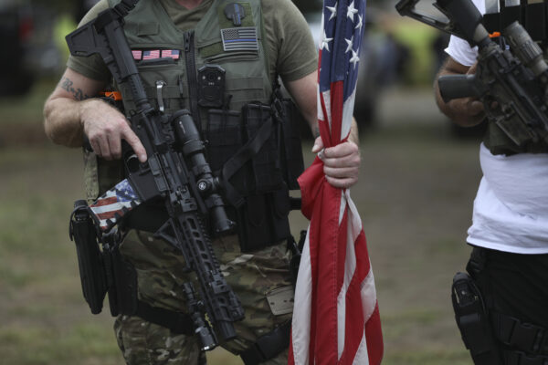 A person holds a weapon and a flag as members of the Proud Boys and other right-wing demonstrators rally on Saturday, Sept. 26, 2020, in Portland, Ore. (AP Photo/Allison Dinner)