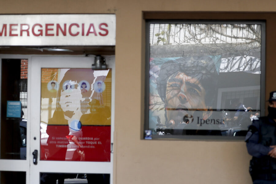 A police officer stands outside the hospital where Diego Maradona is hospitalized and where images of him placed by fans are reflected in the windows, in La Plata, Argentina Tuesday, Nov. 3, 2020. Maradona was admitted to the hospital with signs of depression Monday, three days after his 60th birthday. (AP Photo/ Natacha Pisarenko)