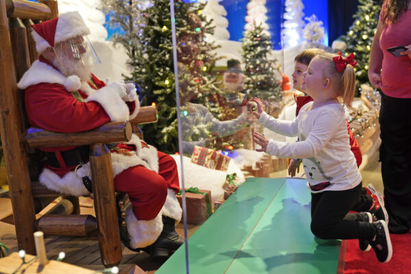 Julianna, 3, and Dylan, 5, Lasczak visit with Santa through a transparent barrier at a Bass Pro Shop in Bridgeport, Conn., Tuesday, Nov. 10, 2020.  Malls are doing all they can to keep the jolly old man safe from the coronavirus, including banning kids from sitting on his knee, completely changing what a Santa visit looks like.   (AP Photo/Seth Wenig)