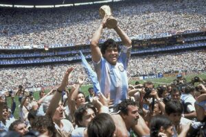 FILE – In this June 29, 1986 file photo, Diego Maradona holds up his team's trophy after Argentina's 3-2 victory over West Germany at the World Cup final soccer match at Atzeca Stadium in Mexico City. The Argentine soccer great who was among the best players ever and who led his country to the 1986 World Cup title before later struggling with cocaine use and obesity, has died. He was 60. (AP Photo/Carlo Fumagalli, File)