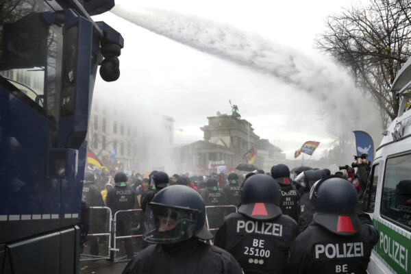 Police uses water canons to clear a blocked a road between the Brandenburg Gate and the Reichstag building, home of the German federal parliament, as people attend a protest rally in front of the Brandenburg Gate in Berlin, Germany, Wednesday, Nov. 18, 2020 against the coronavirus restrictions in Germany. Police in Berlin have requested thousands of reinforcements from other parts of Germany to cope with planned protests by people opposed to coronavirus restrictions. (AP Photo/Michael Sohn)