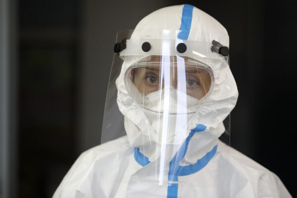 Volunteer dressed in a personal protective suit attends a one-day training organized by Czech Red Cross in Jablonec nad Nisou, Czech Republic, Saturday, Oct. 31, 2020. After the training the volunteers will able to assist medical personnel in hospitals and nursing homes. Over 15,000 medical staff in the country's hospitals have been tested positive for the coronavirus while a number of hospitalized patients has been rising amid a record surge in coronavirus infections. (AP Photo/Petr David Josek)