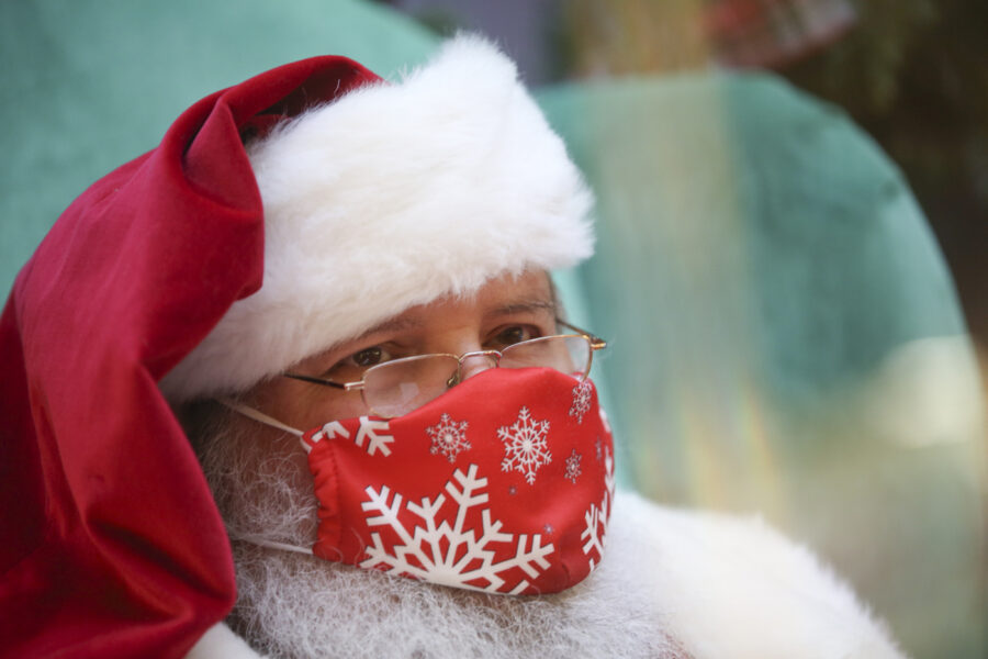 Santa Claus sits behind plexiglass and wears a mask as he waits for children in the Viewmont Mall in Scranton, Pa., on Wednesday, Dec. 9, 2020. (Jake Danna Stevens/The Times-Tribune via AP)
