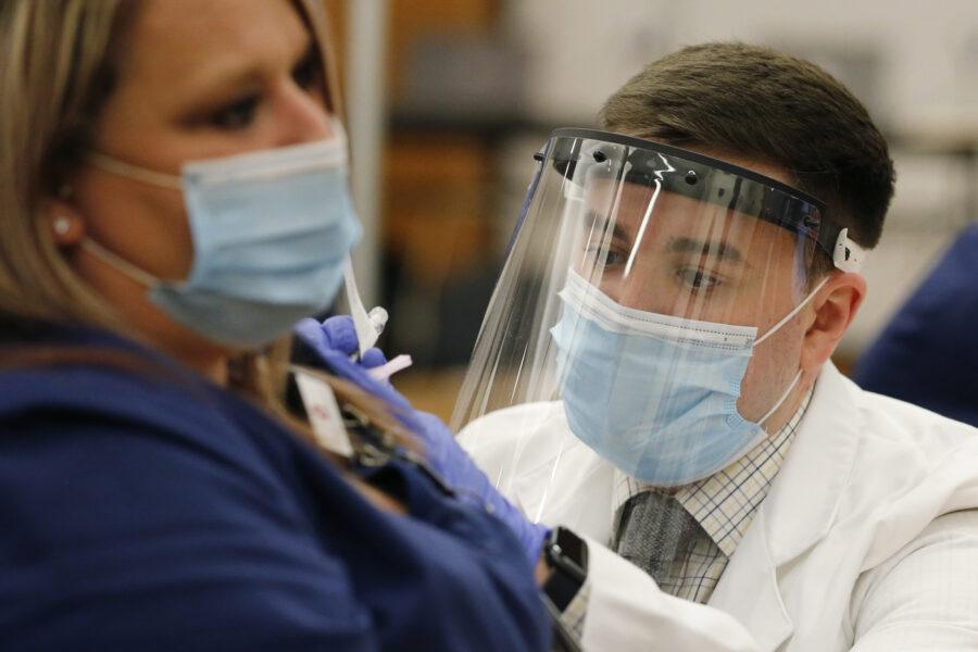 Ohio State employee Cory Coffey, right, administers a Pfizer-BioNTech COVID-19 vaccine Monday, Dec. 14, 2020, in Columbus, Ohio.  (AP Photo/Jay LaPrete)