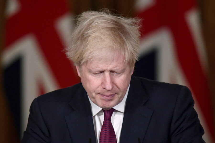 Britain's Prime Minister Boris Johnson speaks during a news conference in response to the ongoing situation with the coronavirus (COVID-19) pandemic, inside 10 Downing Street, London, Saturday, Dec. 19, 2020. Johnson says Christmas gatherings can't go ahead and non-essential shops must close in London and much of southern England as he imposed a new, higher level of coronavirus restrictions to curb rapidly spreading infections. (Toby Melville/Pool Photo via AP)