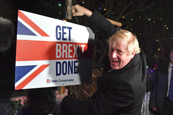 "FILE — In this Wednesday, Dec. 11, 2019 file photo, Britain's Prime Minister and Conservative party leader Boris Johnson poses as he hammers a ""Get Brexit Done"" sign into the garden of a supporter, in Benfleet, England. Britain and the European Union have struck a provisional free-trade agreement that should avert New Year chaos for cross-border traders and bring a measure of certainty for businesses after years of Brexit turmoil.  (Ben Stansall/Pool via AP, File)"