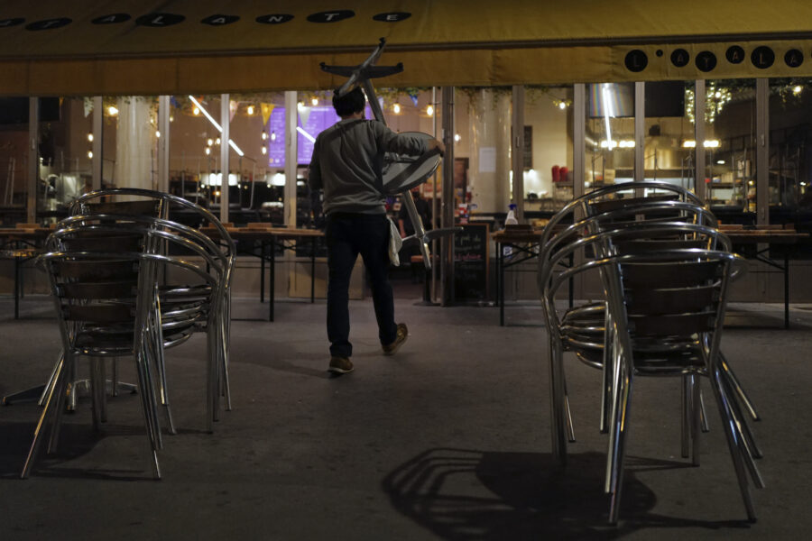 Philippe Cotonnec of the Atalante Bar carries tables to close a bar terrace in Paris, Monday Sept. 28, 2020. French President Emmanuel Macron justified on Monday new restrictions in the country to limit the spread of the virus as restaurant and bar owners forced to shut down expressed anger at the measures. Milder restrictions have been ordered in ten other cities including Paris, with gyms shut down, public gatherings of more than 10 people banned and bars ordered to close at 10 p.m. (AP Photo/Francois Mori)