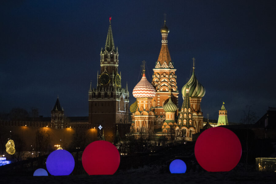 St. Basil Cathedral, right, and Kremlin's Spasskaya Tower illuminated as light balls are installed for New Year and Christmas celebrations in Zaryadye Park in Moscow, Russia, Wednesday, Dec. 23, 2020. (AP Photo/Pavel Golovkin)