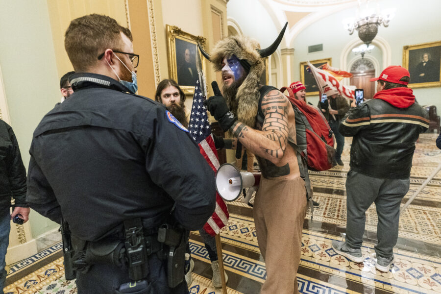 FILE – In this Jan. 6, 2021, file photo supporters of President Donald Trump are confronted by U.S. Capitol Police officers outside the Senate Chamber inside the Capitol in Washington. An Arizona man seen in photos and video of the mob wearing a fur hat with horns was also charged Saturday in Wednesday's chaos. Jacob Anthony Chansley, who also goes by the name Jake Angeli, was taken into custody Saturday, Jan. 9. (AP Photo/Manuel Balce Ceneta, File)
