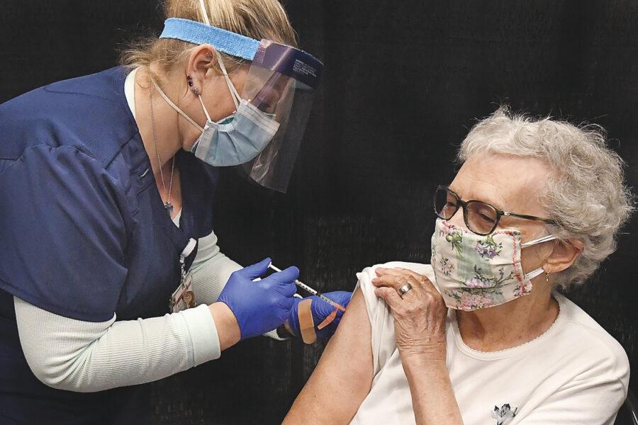 Yuma Regional Medical Center registered nurse Candace Manville, left, administers a COVID-19 vaccine to 94-year-old Edith Robbins at the YRMC vaccination clinic, Thursday, Jan. 28, 2021, inside Yuma Civic Center in Yuma, Ariz. (Randy Hoeft/The Yuma Sun via AP)