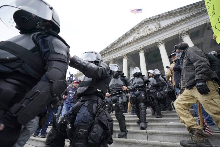 Police in riot gear walk out of the Capitol, Wednesday, Jan. 6, 2021, in Washington. As Congress prepares to affirm President-elect Joe Biden's victory, thousands of people have gathered to show their support for President Donald Trump and his claims of election fraud. (AP Photo/Manuel Balce Ceneta)