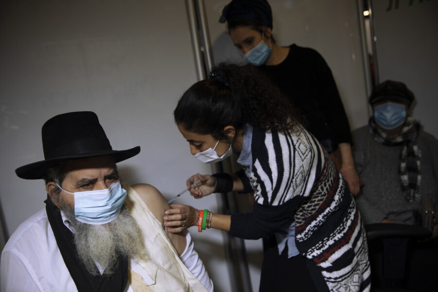 A man receives a coronavirus vaccine from medical staff at a COVID-19 vaccination center in Jerusalem, Monday, Jan. 4, 2021. (AP Photo/Oded Balilty)