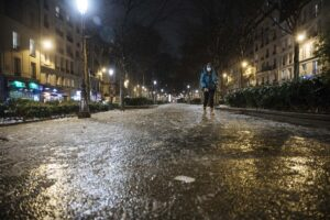 A woman walks in an empty street as the 6 p.m curfew starts in Paris, Saturday Jan.16, 2021. The prime minister announced Thursday an extension of the 6 p.m.-to-6 a.m. curfew to cover the whole country, including zones, like Paris, where it previously hadn't started until 8 p.m. Shopping and all outdoor leisure activities stop at curfew, only short pet walks allowed. Working and commuting allowed with note from employer. Food deliveries but not takeout allowed. Fines for curfew-breakers. (AP Photo/Lewis Joly)