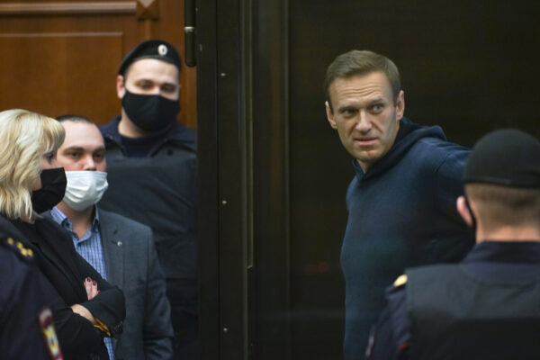 In this handout photo provided by Moscow City Court Russian opposition leader Alexei Navalny talks to his lawyers standing in the cage during a hearing to a motion from the Russian prison service to convert the suspended sentence of Navalny from the 2014 criminal conviction into a real prison term in the Moscow City Court in Moscow, Russia, Tuesday, Feb. 2, 2021. (Moscow City Court via AP)