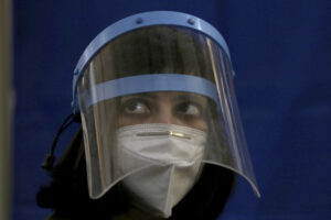 A doctor wears a face mask and shield to protect against the coronavirus while she wait for to receive a Sinopharm coronavirus vaccine at a vaccination center, in Karachi, Pakistan, Wednesday, Feb. 3, 2021. Pakistani authorities started vaccinating frontline health workers on Wednesday amid a steady decline in confirmed cases and fatalities, and days after Pakistan received half a million doses of the Sinopharm vaccine donated by China. (AP Photo/Fareed Khan)